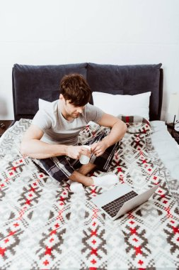 young male freelancer with coffee cup sitting on bed with laptop at home