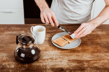 cropped image of man spreading toast by jam at table with coffee pot and cup in kitchen