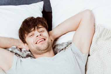 portrait of young man looking at camera and laying in bed during morning time at home