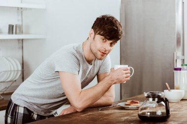 man drinking coffee at table with toasts and coffee pot in kitchen at home