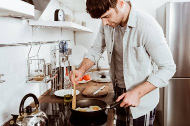 handsome young man making eggs on breakfast in kitchen at home