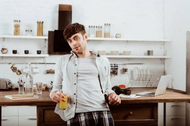 male freelancer with orange juice standing near table with laptop in kitchen at home