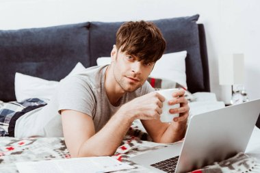 selective focus of male freelancer with coffee cup looking at camera and laying on bed with laptop at home
