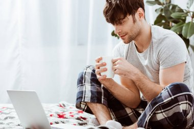 handsome male freelancer with coffee cup sitting on bed with laptop at home