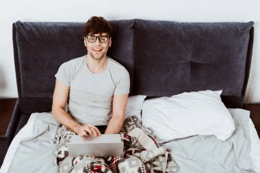 cheerful male freelancer working on laptop and looking at camera in bed at home