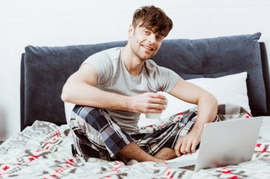smiling male freelancer with coffee cup looking at camera on bed with laptop at home
