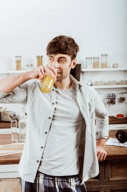 man drinking orange juice on breakfast in kitchen at home