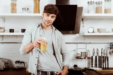 selective focus of young man drinking orange juice on breakfast in kitchen at home