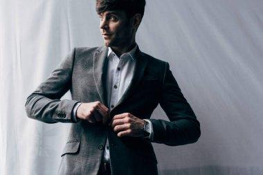 Young handsome businessman adjusting suit jacket stock vector