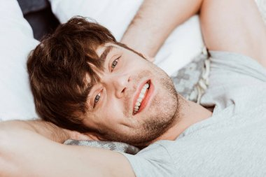 close up portrait of young man looking at camera and laying in bed during morning time at home