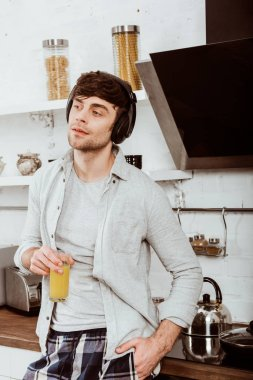 man in headphones holding orange juice on breakfast in kitchen at home