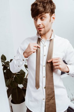 happy businessman in white shirt tying neck tie at home