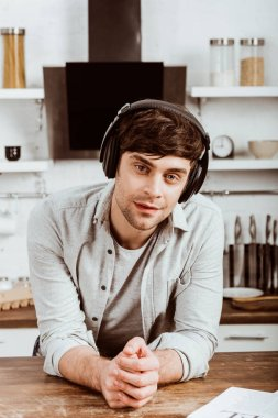 handsome man in headphones listening music and looking at camera in kitchen at home