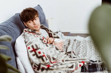 selective focus of sick man wrapped in blanket sitting with cup of tea in bed at home