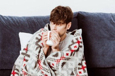 selective focus of sick man wrapped in blanket drinking tea in bed at home