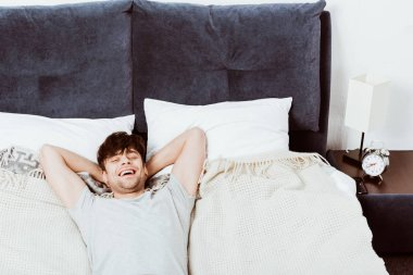 high angle view of laughing young man looking at camera and laying in bed at home