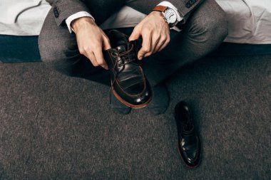 partial view of businessman putting on shoes in bedroom at home