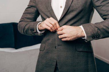 cropped image of businessman buttoning up jacket