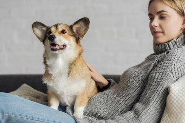 happy young woman relaxing on couch with her corgi dog
