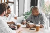 Multikulturelle Geschäftsleute arbeiten am Laptop und diskutieren im Büro über Geschäftsstrategie