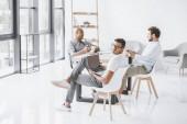 Fotografia gruppo multiculturale di uomini daffari che si siede al posto di lavoro in ufficio moderno luce