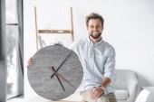 Fotografie portrét usměvavý obchodník s velké hodiny sedět na stole v kanceláři