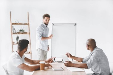 young businessman at white board making presentation to colleagues