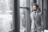 Photo young pensive businessman in suit looking out window in office
