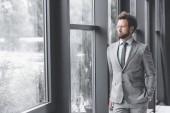 Fotografia giovani uomo daffari pensive in vestito che osserva fuori finestra in ufficio