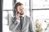 portrét podnikatele v obleku mluvit na telefonu v kanceláři