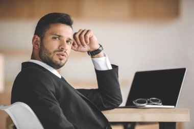 portrait of handsome businessman at workplace with opened laptop in office