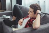s úsměvem teenagera s popcorn sledování filmu na gauči doma