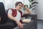 Fotografie usmívající se muž dospívající s popcorn sledování filmu doma