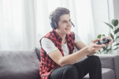 Fotografie happy teenager with headset playing video game with joystick at home