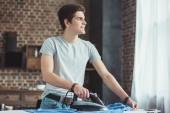 Fényképek álmodozó kaukázusi tinédzser vasalási kék ing otthon