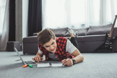 teen boy studying with copybook and laptop while lying on floor