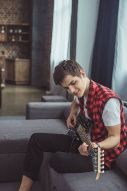 smiling teenager playing electric guitar at home