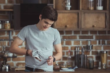 teenager cleaning dinnerware with towel on kitchen