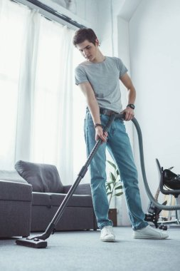 teenager cleaning floor with vacuum cleaner