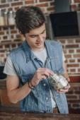 dospívající chlapec uvedení dolarové bankovky do Pokladnička