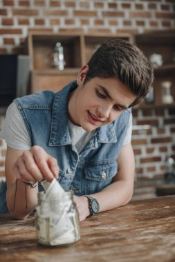 handsome teenager putting dollar banknotes into saving glass jar for money