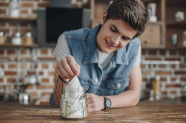 handsome teenager taking dollar banknotes from saving glass jar for money