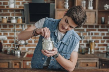 smiling teenager taking dollar banknotes from saving glass jar for money