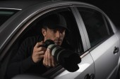 Paparazzi mit Mütze spionieren mit Kamera aus seinem Auto