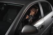 Paparazzi überwachen ihn mit Objektglas aus seinem Auto