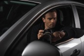 male paparazzi looking at wristwatch and spying by camera with lens from his car
