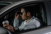 titkos férfi ügynök tesz megfigyelő távcső, és kávét iszik az autó oldalnézetből
