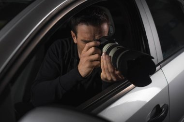 male paparazzi doing surveillance with camera from his car