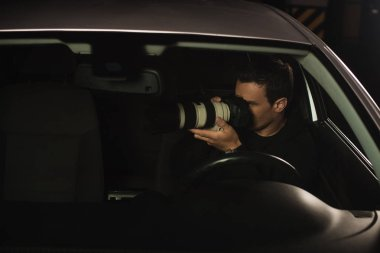 paparazzi doing surveillance by camera from his car
