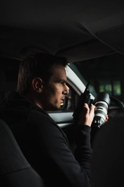 side view of male paparazzi doing surveillance by camera and using talkie walkie in car